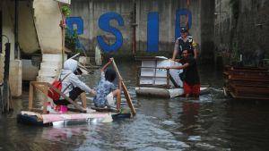 Indonesier transporterar valurnor på en flotte.