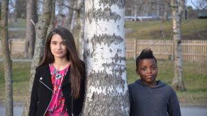 Asta och Valter står på varsin sida av ett träd och ser in i kameran.