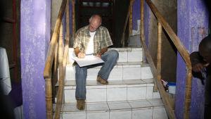 Polisen Thomas Elfgren sitter i en trappa och antecknar i ett stoirt block.