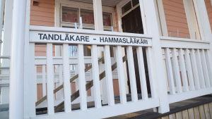Trappan och trappräcket till tandmottagningen i Ekenäs. Skylt där det står tandläkare-hammaslääkäri på trappräcket.
