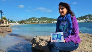 """En kvinna sitter vid en sandstrand med en skylt med texten """"Plastic Free Ibiza"""" i famnen."""