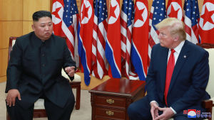 Pohjois-Korean johtaja Kim Jong-un ja Yhdysvaltain presidentti Donald Trump istuvat maiden lippujen edessä ja keskustelevat