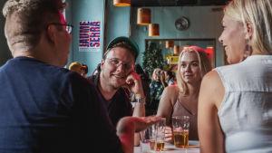 Två män och två kvinnor sitter vid ett restaurangbord och pratar och dricker öl.
