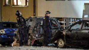 Två män i polisuniformer står på en gata eller en gård framför bilar skadade av en explosion.  Kriminaltekniker arbetar på platsen efter den kraftig explosionen som inträffade i under natten mot måndagen på Östermalm i Stockholm den 13 januari 2020..