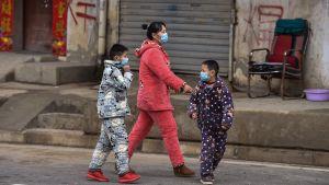 På bilden syns en mamma med sina två barn promenera i Wuhan iklädda ansiktsmasker.