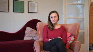 Monica Ålgars sitter i en ljusröd fåtölj.