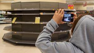 Bild på en person som tar bild på en tom butikshylla.