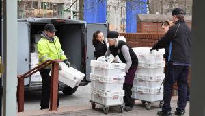 Personer lastar matvaror ur en paketbil.