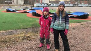 Två flickor framför en skatebordpark.