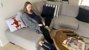 Carina Bruun sitter höggravid på soffan och hennes två-åring ligger på golvet.