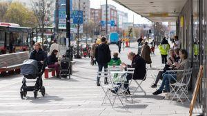 Stadsbild från Stockholm med folk som promenerar på gatan och sitter på uteservering.
