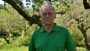 Mikko Hupa, en man med glasögon och grön skjorta, står bland äppelträd.