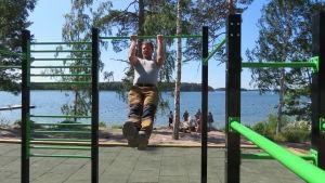 En man jumppar, drar armhävningar på ett utegym. Sommar, sol, hav i bakgrunden.
