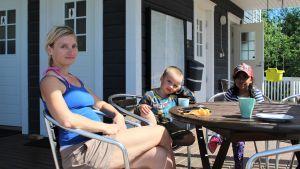 En kvinna med två barn sitter på en uteservering.