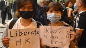 """Två kvinnor i munskydd håller upp skyltar där det på engelska står """"berfria Hongkong"""" och """"vår tids revolution"""""""