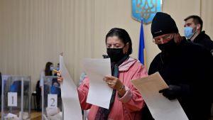 Två personer i munskydd läser från papper.