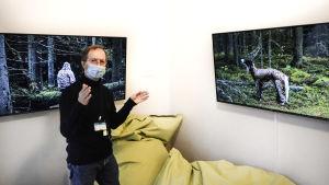 Man med munskydd visar två skärmar i ett rum. På skärmarna bilder från skog.