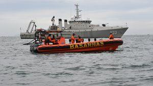 En gummibåt med räddningspersonal ombord och i bakgrunden ett fartyg från marinen.