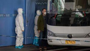Personer med munskydd omgivna av vakter i vita heltäckande skyddsdräkter stiger på en vit buss.