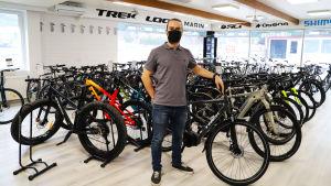 Aleksi Sanaksenaho står framför en stor rad cyklar i en cykelaffär.