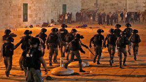 En stor grupp poliser närmar sig en hop civila.