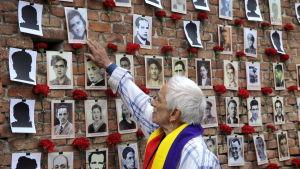 Mies katselee valokuvia Espanjan sisällissodan muistoseinällä.