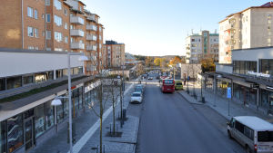 Gata med bilar, en buss och bostadshus på bägge sidor.