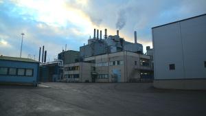 Bild av den äldsta fabriksbyggnaden på Fermions fabriksområde i Hangö. Rök kommer ur skorstenarna på taket och det är en varm decemberdag med moln på himlen.