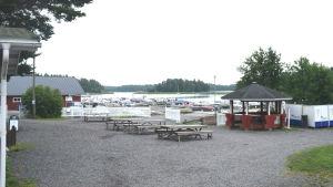 En hamn, i förgrunden syns bord och bänkar och i bakgrunden småbåtar som ligger vid bryggor nära stranden. I bakgrunden öar och vatten.