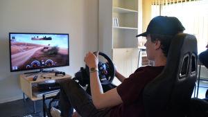 Bild på Janne Lipponen som spelar rally i en simulator framför tv:n.