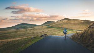 pyöräilijä polkee mäkistä tietä