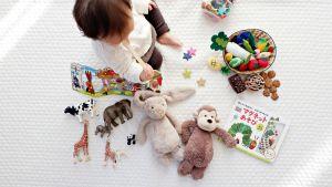 Lapsi istuu lattialla valkoisen viltin päällä lelujen keskellä.