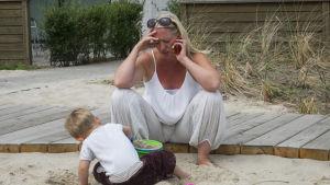 Barn sitter vid sandlåda med sin mamma som ser stressad ut och pratar i sin mobil