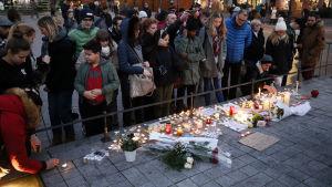 Sörjande människor står vid platsen för våldsdådaet och har lagt ned ljus och blommor på marken.