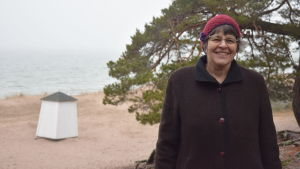 En kvinna iklädd vinterkläder poserar framför en strand med tallar och sanddyner.