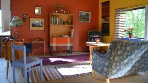 """Ett """"vardagsrum"""" i ett museum. Inrett i 1960-talsstil med smäcker soffa, gammal tv, teakmöbler."""
