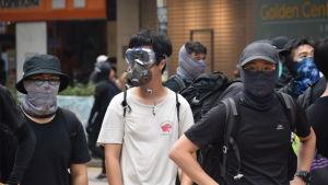 Demonstranterna använder masker dels för att skydda sig och dels för att dölja sin identitet. Hårda straff väntar dem som blir dömda för att ha deltagit i upplopp.