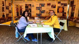 Två människor sitter mittemot varandra vid ett bord i ett gult tält.