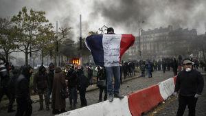 Man under demonstration håller upp fransk flagga.