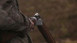 Hand som håller jaktvapen