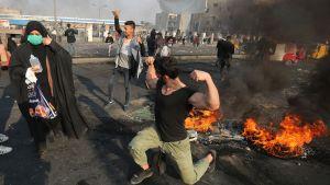 En av demonstranterna på Tayaran-torget passade på att spänna musklerna mitt bland de brinnande bildäcken.