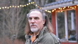 En man med bakåtkammat, långt mörkt, gråsprängt hår. Ute. Vinter, ingen snö, en ljuskedja i bakgrunden.
