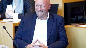 Thomas Kemmerich sitter framför en mikrofon och ler. Han tittar åt sidan och sitter med händerna ihop.