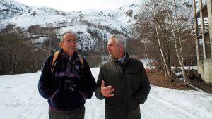 Två gråhåriga män står och diskuterar i ett snöigt landskap.