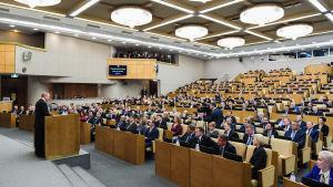 Vladimir Putin som står och pratar inför ryska duman.