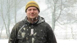 En man i gul mössa och grå jacka står på en åker i ymnigt snöfall.