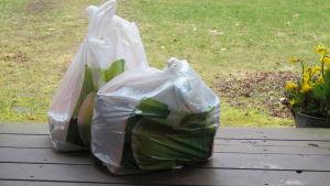 Två plastkassar med matvaror ställda ute på en trappa.