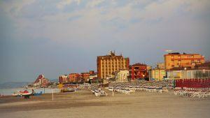 Tom strand i Italien med tomma badstolar och i bakgrunden syns byggnader.