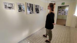 En kvinna står och tittar på fotografier på en vägg.