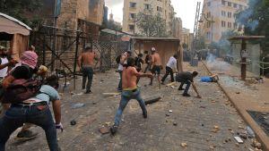 Demonstranter kastar sten mot kravallpolis.